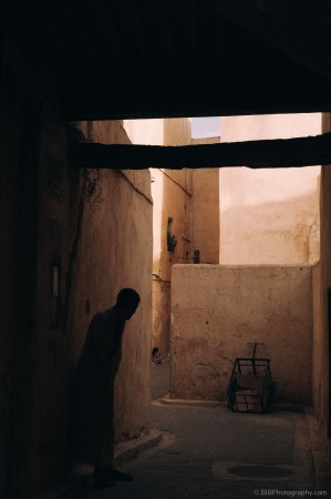 A man is having a call in the twilight, a girl is backing onto the wall in the background- Fes, Morocco
